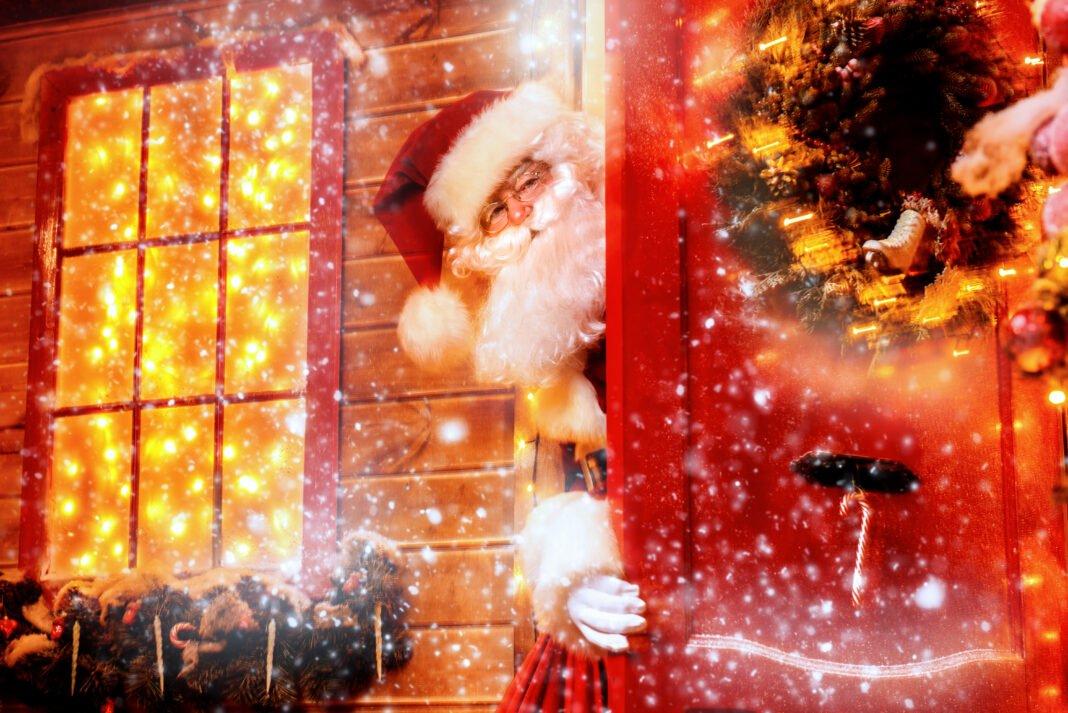 Santa Claus peeking out from behind festive door