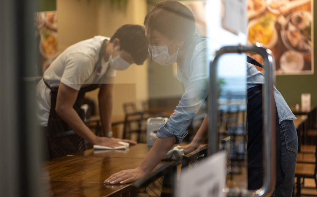 Waiter wearing protective face mask while cleaning tables in restaurant