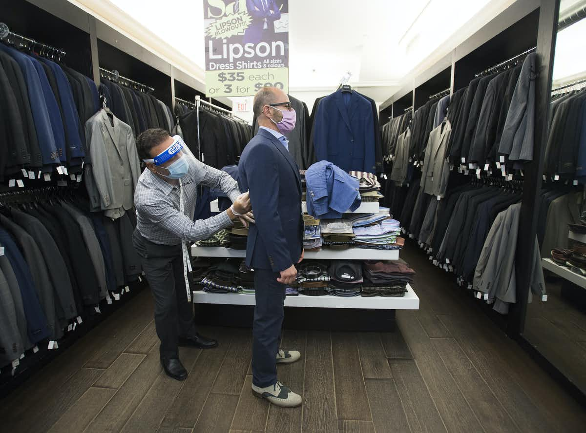 Head tailor Soheil Khorrami, left, demonstrates a safe way to fit a blazer for a customer at Tom's Place in Kensington Market in Toronto in June 2020. THE CANADIAN PRESS/Nathan Denette