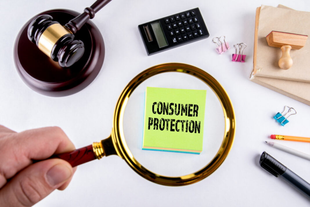 Consumer protection, law and justice concept with man's hand holding magnifying glass.