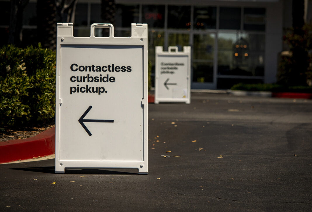 Sign advertising contactless curbside pickup at retail store parking lot