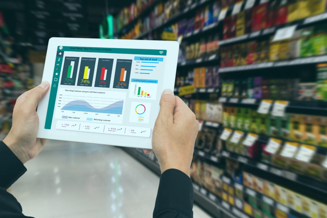 Retailer holds tablet and use augmented reality technology to monitor data.