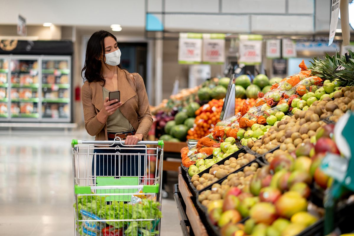 Woman grocery shops with face mask on during COVID-19 pandemic.