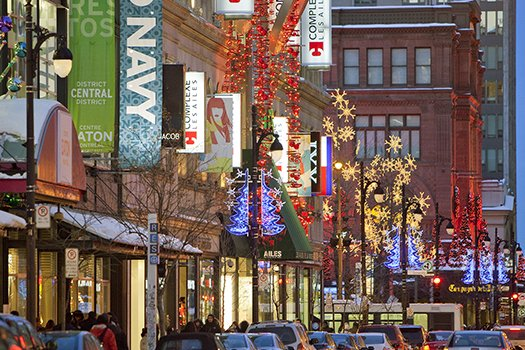 Sainte-Catherine Street storefronts adorned/aglow with Christmas lights