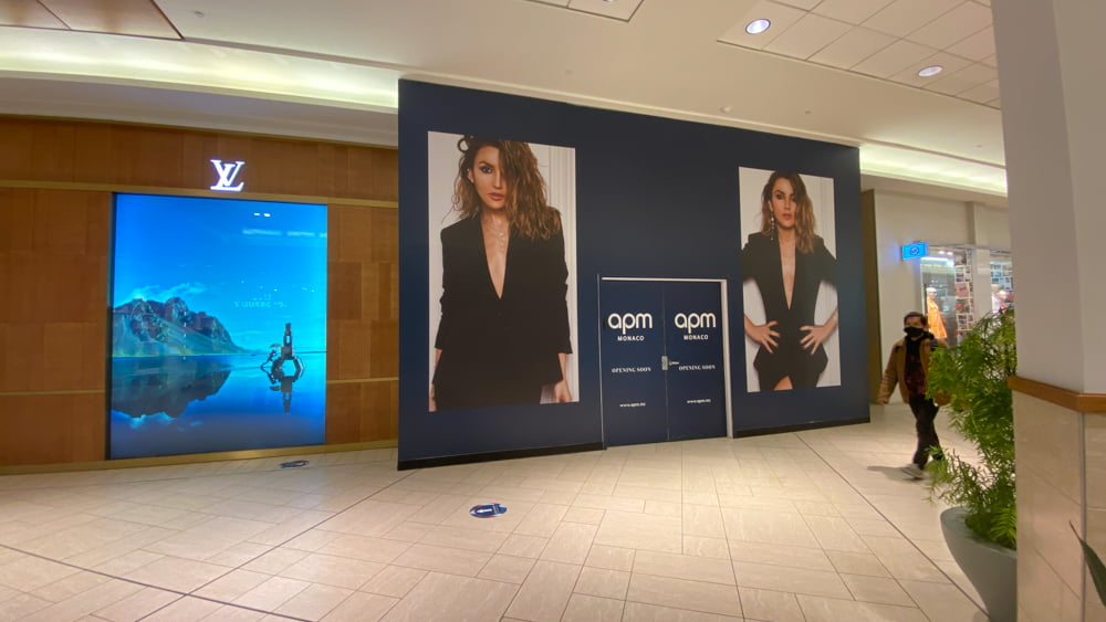 """""""Opening Soon"""" signage for APM Monaco on lower level of CF Chinook Centre"""